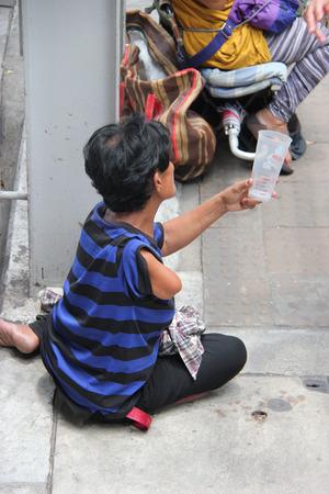 insufficient: Bangkok Thailand  April 30 2015: Handicapped beggar is begging for money from pedestrians near a skytrain station.