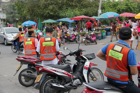 Bangkok Thailand  May 2 2015: Motorcycle Taxis with orange vests common form of public transportation in Bangkok are waiting for customers at a market. Locals use the service when they need to get somewhere fast. They are popular for delivery service as t
