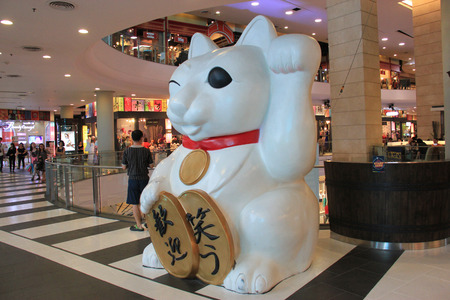 to beckon: Bangkok, Thailand - April 30, 2015: The maneki-neko or beckoning cat, a Japanese figurine believed to bring good luck to the owner, is used to decorated for Tokyo theme on the first floor of Terminal 21.
