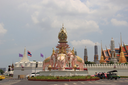 reigns: Bangkok, Thailand - May 8, 2015: The statues of White Elephants, the sign that the monarch reigns with justice and power, are holding the symbol of King Rama 9 over their heads in front of Emerald Buddha Temple.