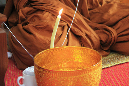 cleric: Buddhist monks are blessing holy water by praying, and pouring melted candle tear to the water.