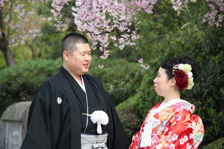 Osaka, Japan - April 8, 2015: Japanese couples in Japanese traditional costumes are taking pre-wedding photos together at Osaka Castle Park. 에디토리얼