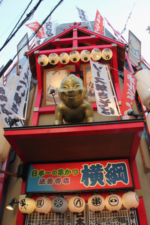 characterized: Osaka, Japan - April 8, 2015: Dotonbori, one of the principal tourist destinations in Osaka, is a popular nightlife and entertainment area characterized by its eccentric atmosphere and large illuminated signboards.