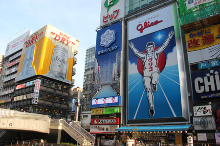 finishing line: Osaka, Japan - April 8, 2015: Glico billboard displaying the image of a runner crossing a finishing line and Asahi billboard are icons of Osaka, Japan. They are located in Dotonbori, a famous tourist destination for nightlife and entertainment area. Editorial