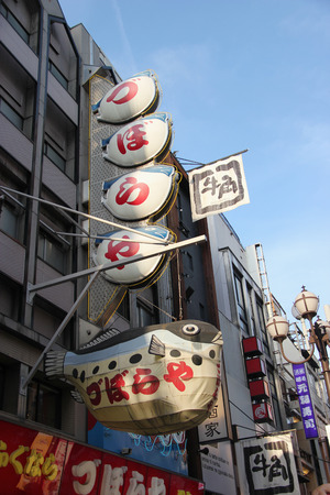 characterized: Osaka, Japan - April 8, 2015: Blowfish restaurant at Dotonbori, a popular nightlife and entertainment area characterized by its eccentric atmosphere and large illuminated signboards in Osaka, Japan. Editorial