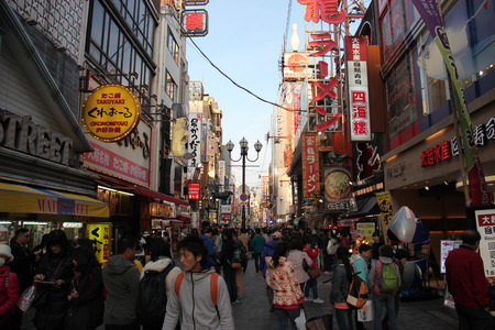 cuisine entertainment: Osaka, Japan - April 8, 2015: Dotonbori, one of the principal tourist destinations in Osaka, is a popular nightlife and entertainment area characterized by its eccentric atmosphere and large illuminated signboards.