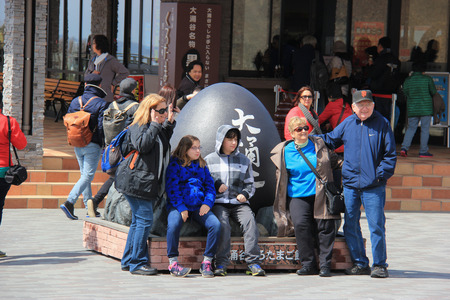 Hakone, Japan - April 9, 2015: Tourists are taking photos with Black Egg sculpture at Owakudani, well known for black eggs or eggs hard-boiled in hot springs. Consuming the eggs is said to increase longevity. Editorial