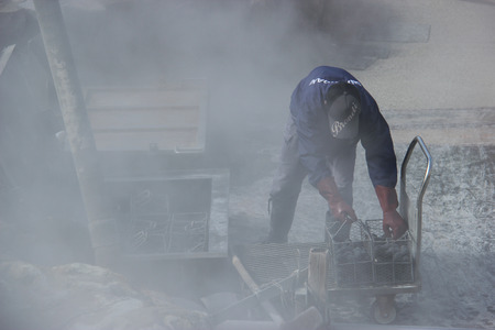 7 9 years: Hakone, Japan - April 9, 2015: Unidentified man is boiling black eggs believed to help extend 7 years of life if eating one at Owakudani, a volcanic valley with active sulphur vents and hot springs.