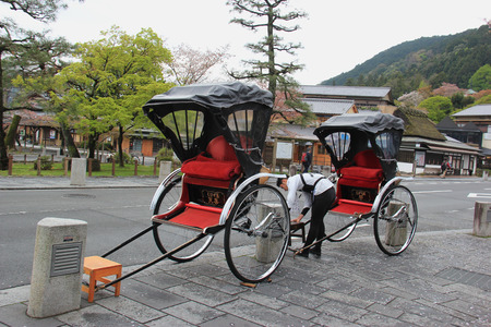 locking up: Kyoto, Japan - April 11, 2015: Rickshaw driver is locking up his rickshaw, traditional transportation in Arashiyama, which is a nationally designated Historic Site and Place of Scenic Beauty.