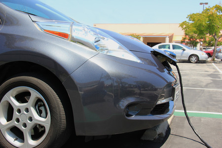 electric power station: Electric Car is being plugged into charging station for power supply.