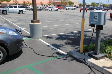 electric power station: Downey, California - July 28, 2015: Electric Car is being plugged into charging station for power supply.