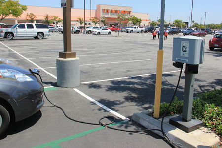 electric power station: Downey, California - July 28, 2015: Electric Car is being plugged into charging station for power supply at Home Depot.