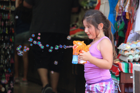 watergun: Los Angeles, California, USA - August 14, 2015: Cute girl is having fun playing with bubble coming out of her watergun.