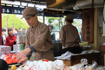 food shop: Tokyo, Japan - April 12, 2015: Japanese merchants are selling snacks to customers at Nakamise Dori, one of the oldest shopping streets in Japan. Editorial