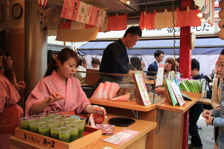japanese people: Tokyo, Japan - April 12, 2015: Japanese merchants are selling snacks to customers at Nakamise Dori, one of the oldest shopping streets in Japan. Editorial