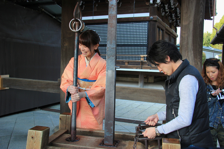 maiko: Kyoto, Japan - April 11, 2015: Tourists are trying out ancient equipment at Kiyomizudera, one of the most celebrated temples of Japan. Editorial