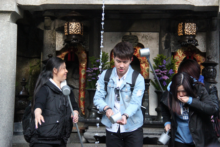 fortunate: Kyoto, Japan - April 11, 2015: Visitors use cups attached to long poles to drink water from 3 streams of Otowa Waterfall at Kiyomizudera wishing in longevity, success in school and a fortunate love life.