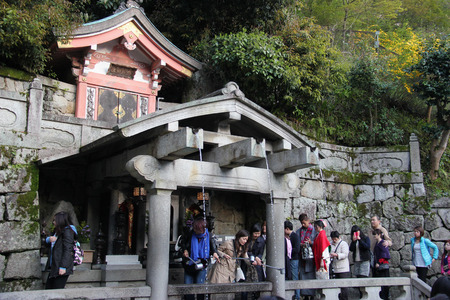 love of life: Kyoto, Japan - April 11, 2015: Visitors use cups attached to long poles to drink water from 3 streams of Otowa Waterfall at Kiyomizudera wishing in longevity, success in school and a fortunate love life.