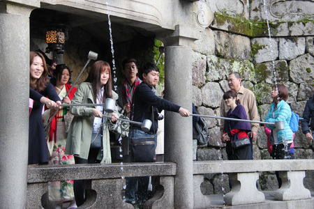 respectful: Kyoto, Japan - April 11, 2015: Visitors use cups attached to long poles to drink water from 3 streams of Otowa Waterfall at Kiyomizudera wishing in longevity, success in school and a fortunate love life.