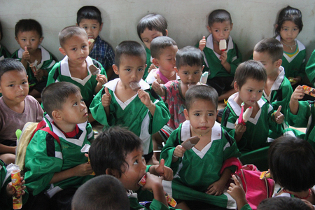 Kanchanaburi, Thailand - July 21, 2013: Poor children enjoy having ice cream after people donate them food.