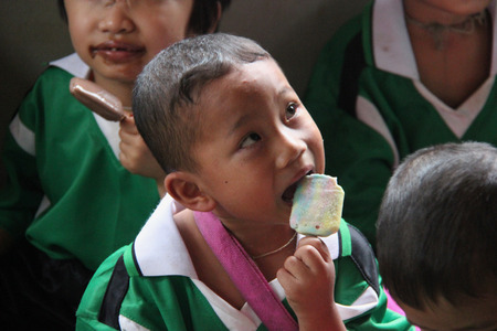 impoverish: Kanchanaburi, Thailand - July 21, 2013: Poor children enjoy having ice cream after people donate them food.