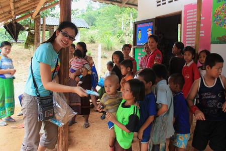 niños pobres: Kanchanaburi, Tailandia - 21 de julio de 2013: Los niños pobres hacen cola para conseguir telas donadas por voluntarios.