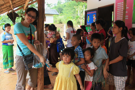 saintliness: Kanchanaburi, Thailand - July 21, 2013: Poor children line up to get donated stuffs from volunteers. Editorial