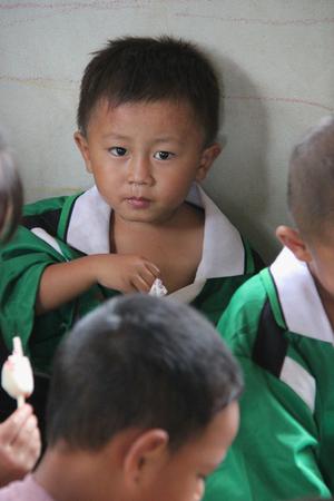POBRES NI�OS: Kanchanaburi, Tailandia - 21 de julio de 2013: Los ni�os pobres disfrutan de tener helado despu�s la gente los donan alimentos.