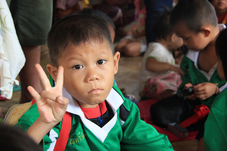 saintliness: Kanchanaburi, Thailand - July 21, 2013: Unidentified boy is trying to make a hand symbol to volunteers after receiving donated stuffs received from them.