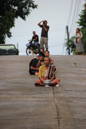 Kanchanaburi, Thailand - July 22, 2013: Buddhists are waiting for monks to offer food in the morning in Sangkhlaburi, Kanchanaburi, Thailand. Editorial