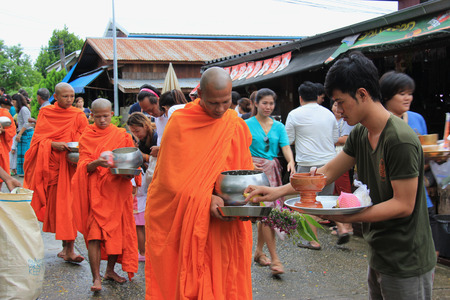 ordination: Kanchanaburi, Thailand - July 22, 2013: Buddhists are offering food to monks in the morning in Sangkhlaburi, Kanchanaburi, Thailand.