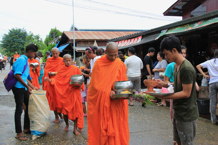 sainthood: Kanchanaburi, Thailand - July 22, 2013: Buddhists are offering food to monks in the morning in Sangkhlaburi, Kanchanaburi, Thailand.