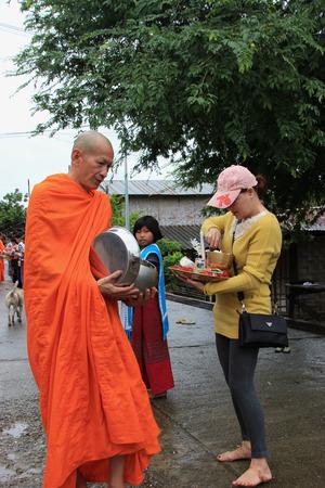 Kanchanaburi, Thailand - July 22, 2013: Buddhists are offering food to monks in the morning in Sangkhlaburi, Kanchanaburi, Thailand.