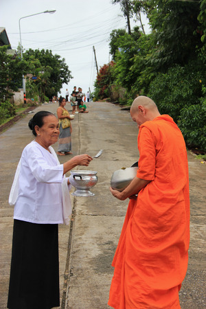 saintliness: Kanchanaburi, Thailand - July 22, 2013: Buddhists are offering food to monks in the morning in Sangkhlaburi, Kanchanaburi, Thailand.