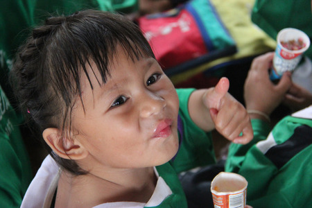 impoverish: Kanchanaburi, Thailand - July 21, 2013: Young cute girl enjoys having ice cream after people donate her food.