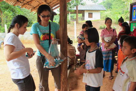 Kanchanaburi, Thailand - July 21, 2013: Poor children line up to get donated stuffs from volunteers. 報道画像
