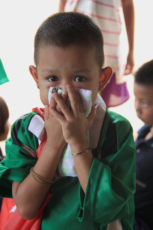 Kanchanaburi, Thailand - July 21, 2013: Unidentified boy is being happy to receive donated stuffs from volunteers.
