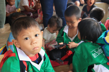 saintliness: Kanchanaburi, Thailand - July 21, 2013: Mon children are waiting for donated stuffs from volunteers. Editorial