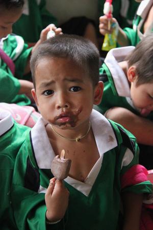 niños pobres: Kanchanaburi, Tailandia - 21 de julio de 2013: Los niños pobres disfrutan de tener helado después la gente los donan alimentos.