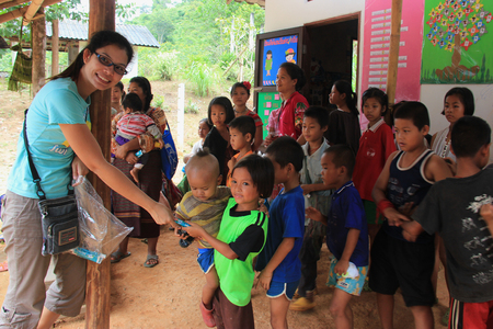 カンチャナブリ、タイ - 2013 年 7 月 21 日: 貧しい子どもたちは、ボランティアから寄付された原料を得るために並べる。 報道画像