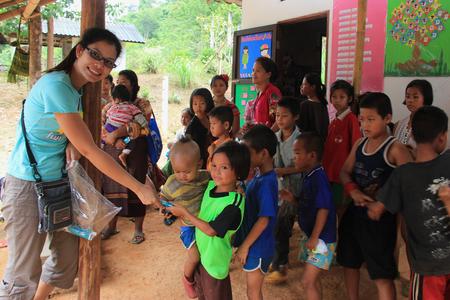 POBRES NI�OS: Kanchanaburi, Tailandia - 21 de julio de 2013: Los ni�os pobres hacen cola para conseguir telas donadas por voluntarios.