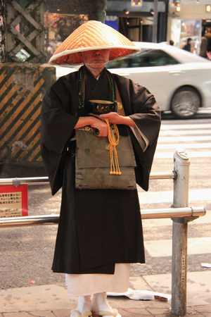 cleric: Tokyo, Japan - April 12, 2015: Japanese priest is standing near Ameya Yokocho, a market street between Okachimachi and Ueno Station.