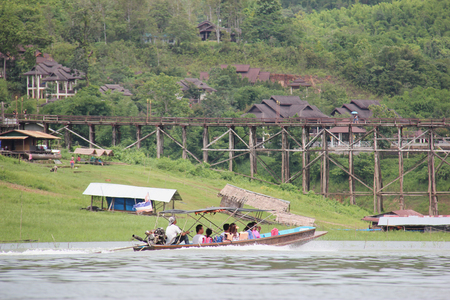 wiwekaram: Kanchanaburi, Thailand - July 22, 2013: Tourists are traveling on a boat to Saphan Mon or Mon Bridge, the longest handmade wooden bridge in Thailand.