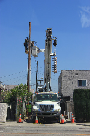 linemen: Huntington Park, California, USA - July 16, 2015: Electrical linemen on a large boom truck are installing electricity line on a wooden pole.
