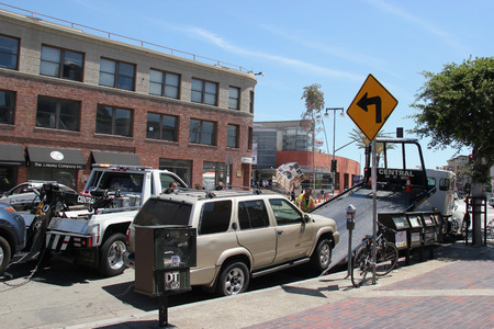 maltreatment: Los Angeles, California, USA - August 16, 2015: Police are towing away vehicles parked beside the street for parking violation.