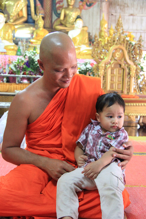 saintliness: Kanchanaburi, Thailand - July 22, 2013: Abbot of Wang Wiwekaram Temple, the most important and revered Buddhist temple in Sangkhla Buri district, is holding a cute young boy. Editorial