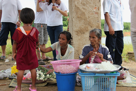 destitute: Kanchanaburi, Thailand - July 22, 2013: Unidentified people are selling flowers to tourists to pay respect to Wat Saam Prasob or The Sunken Temple, the last remaining vestige of the old town flooded for the creation of Khao Laem Reservoir, in Sangkhlaburi