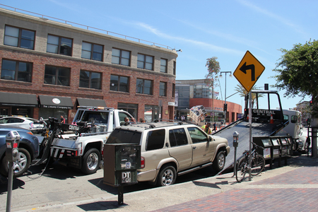 violation: Los Angeles, California, USA - August 16, 2015: Police are towing away vehicles parked beside the street for parking violation.