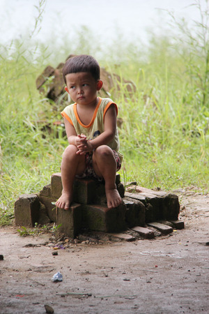 impoverish: Kanchanaburi, Thailand - July 22, 2013: Unidentified boy sitting at Wat Saam Prasob or The Sunken Temple, the last remaining vestige of the old town flooded for the creation of Khao Laem Reservoir, in Sangkhlaburi, Kanchanaburi, Thailand. Editorial