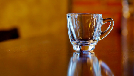 Clear small coffee or tea cup on wood table and black background with reflection and have space for write wording, empty glass comparing empty brain that available for adding new knowledge